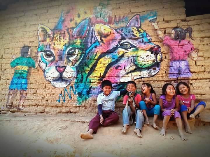 Niños sonriendo frente a un mural de arte urbano del artista MonyerGH